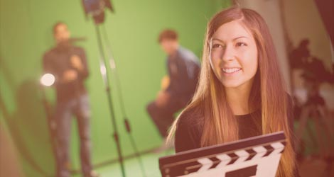 Studentin mit Filmklappe vor Green Screen